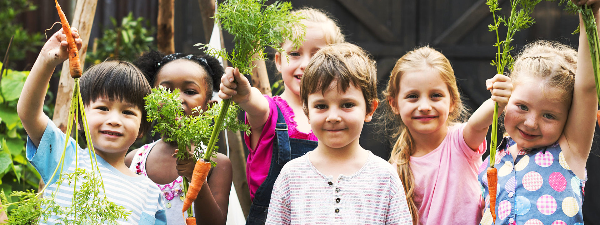 group of smiling children holding a carrots
